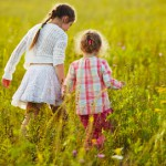 Two little girls are walking among the wildflowers